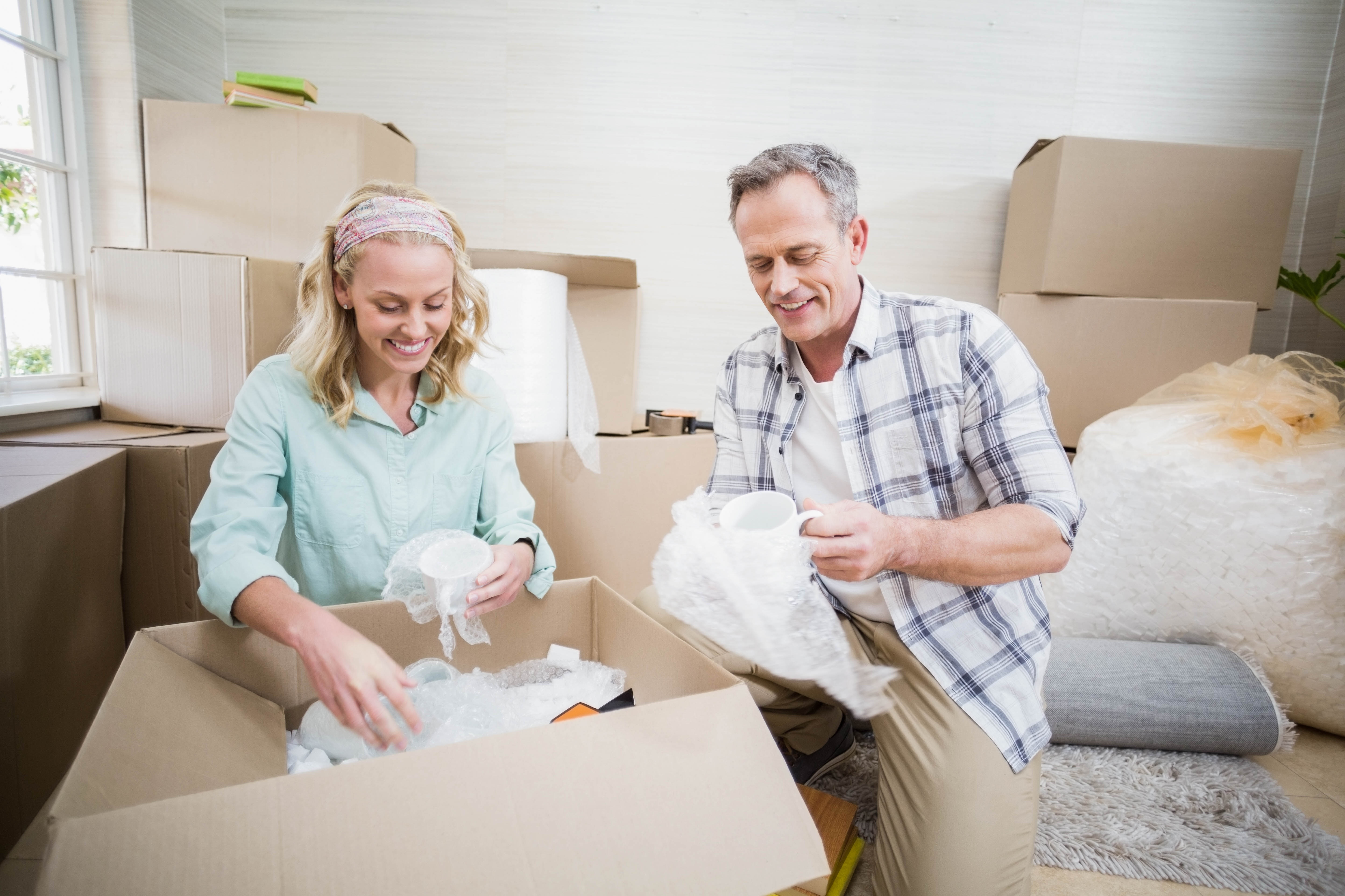 Smiling couple packing mug in a box