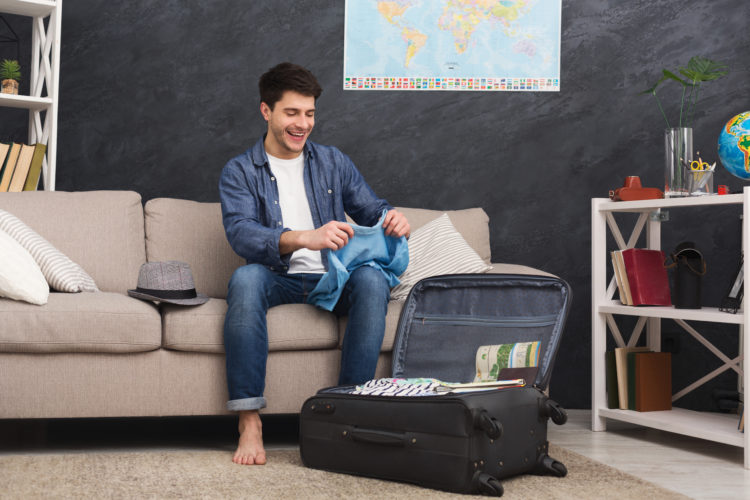 young man packing clothes into a suitcase