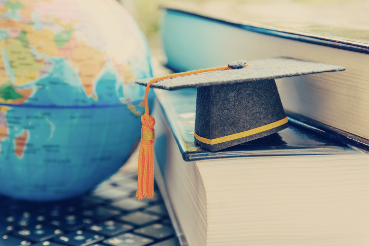 graduation cap on books with a globe