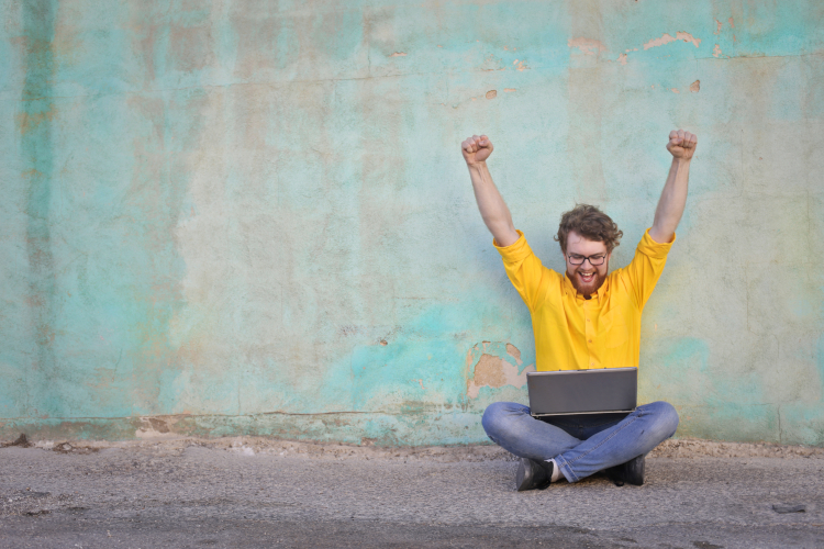 Young man celebrating with laptop