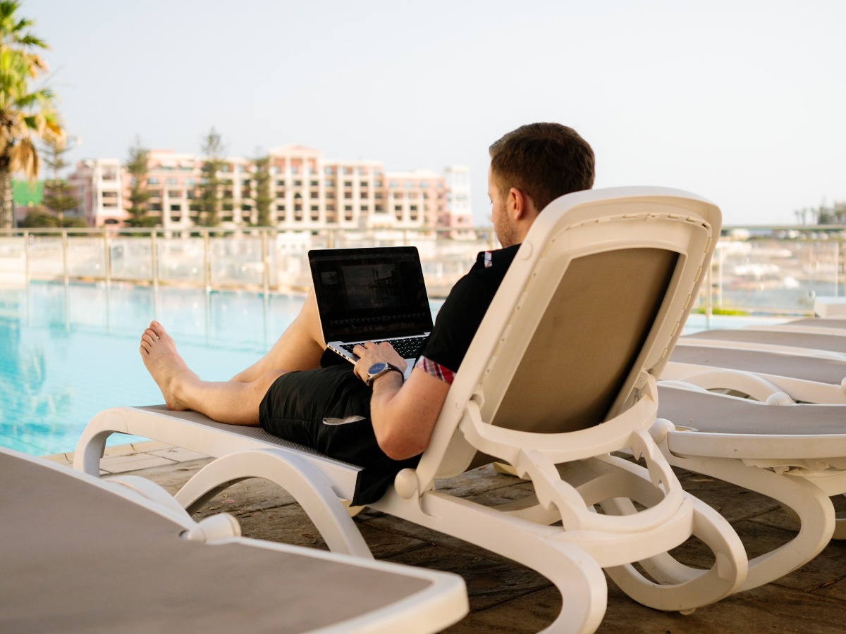 Man browsing computer by pool